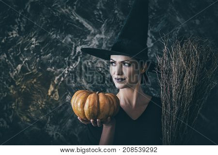 Halloween Witch holding a pumpkin and a broom. woman dressed like a fairy witch