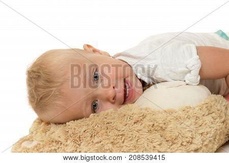 Studio shot of smilling toddler girl lying on a plush toy