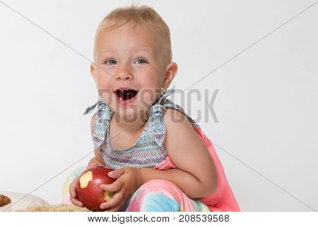 Studio shot of lauhging toddler girl sitting on the plush toy and holding red apple