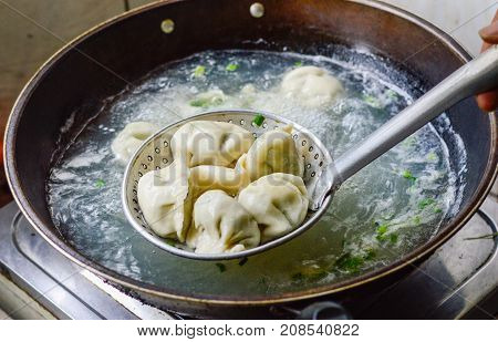 Chinese Boiled Dumplings. The dumplings are picked up from the wok.
