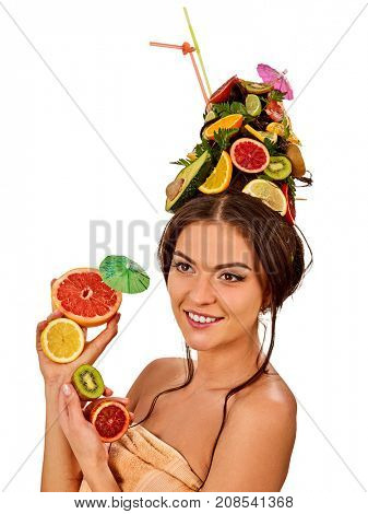 Girl drinking fruit cocktail on summer party. Woman with fresh fruits hairstyle and bare back hold halves of grapefruit with cocktail umbrella. Acceleration of hair and eyebrows growth.