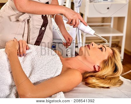 High frequency machine in spa salon. Young woman receiving electric darsonval facial massage after procedure at beauty room close up. Removal of acne from surface of face. The best spa salon.
