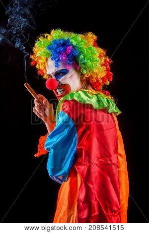 Evil clown on black background. Halloween mad woman is smoking cigar on black background. Portrait of crazy female with an angry look after performance.