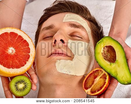 Facial mask from fresh fruits and clay for man. Beautician apply slices of avocado, grapefruit and kiwi. Avocados main ingredient cosmetic masks. Healing clay for the face.