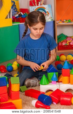 Children building blocks in kindergarten. Group kids playing toy on floor. Top view of interior preschool. Kid is keen on playing dice. Child plays alone.