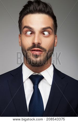 young cross eyed business man smiling on grey background