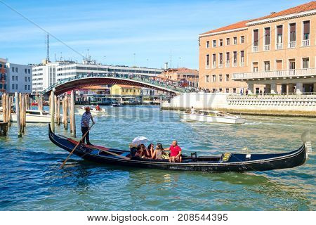VENICE,ITALY - JULY 26,2017 : Tourists on a gondola at the Grand Canal near the Constitution Bridge in Venice