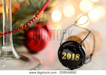 sparkling wine or champagne cork on table with christmas or new year 2018 blurred background and decorated fir-tree