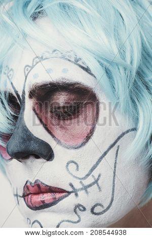 closeup of a bride with a mexican calaveras makeup and short blue hair
