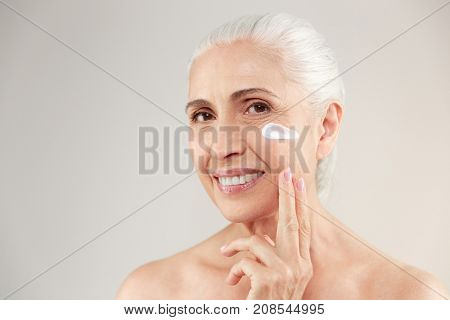 Beauty portrait of a smiling half naked elderly woman applying face cream isolated over white background