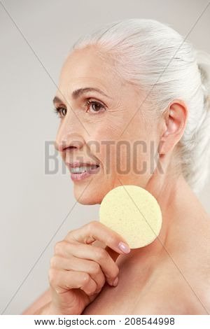 Side view beauty portrait of a happy half naked elderly woman holding make-up sponge at her face and looking away isolated over white background