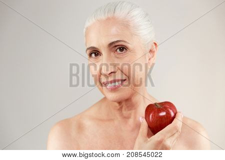 Beauty portrait of a smiling half naked elderly woman holding red apple and looking at camera isolated over white background