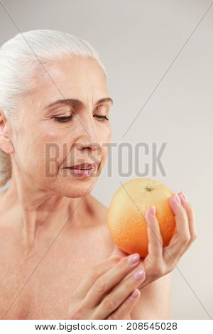 Beauty portrait of an attractive half naked elderly woman holding and looking at an orange isolated over white background