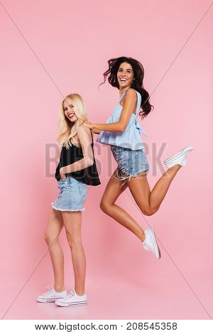 Full length image of two cheerful friends playing and rejoice in studio while looking at the camera over pink background