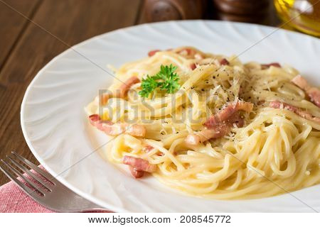 Classic Pasta Carbonara. Spaghetti With Bacon, Egg Yolk And Parmesan Cheese On White Plate On Dark W