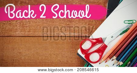 Back to school text against white background against colorful pencils on book