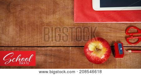 Back to school text over white background against overhead view of apple with ruler and tablet