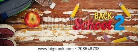 Back to school graphic against overhead view of bag with bottle and apple on table