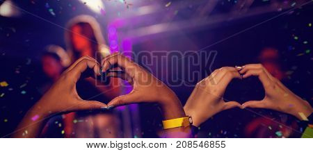 Flying colours against hands of audience forming heart shape during stage show
