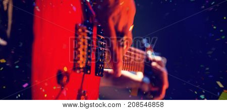 Flying colours against close-up of guitarist playing guitar on stage