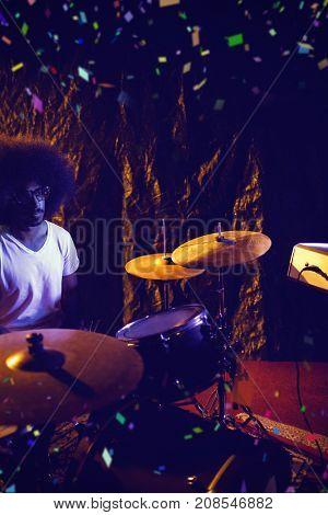 Flying colours against male drummer performing in nightclub