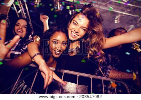 Flying colours against portrait of happy friends enjoying at nightclub
