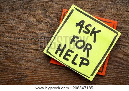 Ask for help advice or reminder - handwriting on a sticky note against rustic wood