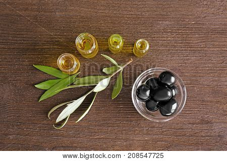 Glass bottles with olive oil on wooden table