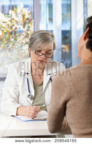 Serious mature female doctor sitting at desk in doctor's room listening to patient, writing paperwork.