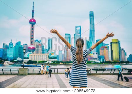 Happy success person with arms up against Shanghai skyline on The Bund. China travel concept or urban lifestyle. Happiness healthy living people in modern city. Woman winning goal challenge.