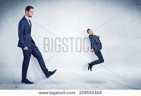 Big businessman kicking small businessman who is flying away with his briefcase on his hand