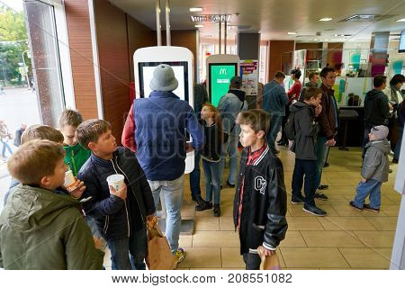 SAINT PETERSBURG, RUSSIA - CIRCA SEPTEMBER, 2017: people use ordering kiosks at McDonald's restaurant. McDonald's is an American hamburger and fast food restaurant chain.
