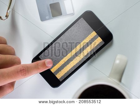Digital composite of Hand touching phone with road