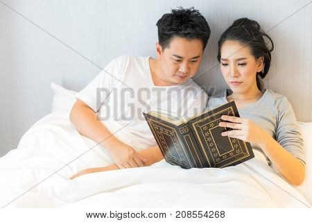 Young Asian Couple laid in a bed reading a book in bedroom of contemporary house for modern lifestyle concept