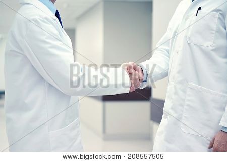 healthcare, profession, people and medicine concept - close up of doctors making handshake