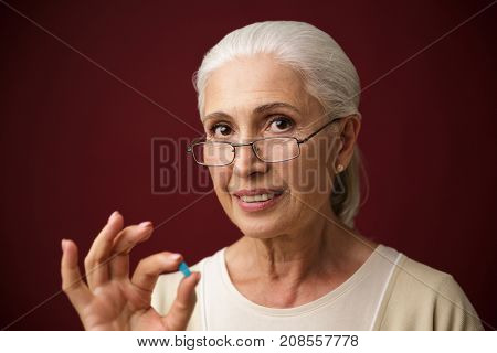 Photo of cheerful old woman sitting over dark red background showing okay gesture. Looking camera.