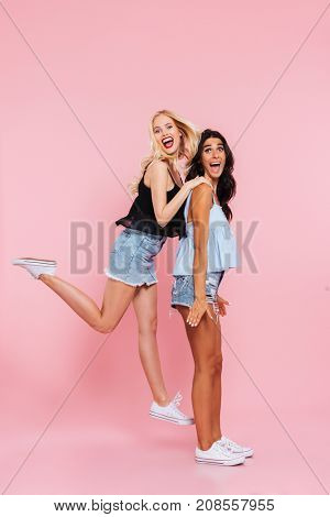 Full length image of two happy friends playing and rejoice in studio while looking at the camera over pink background