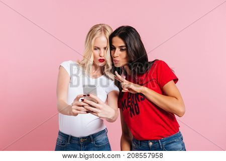 Young friends ladies gesturing and grimacing while making selfie on smartphone isolated