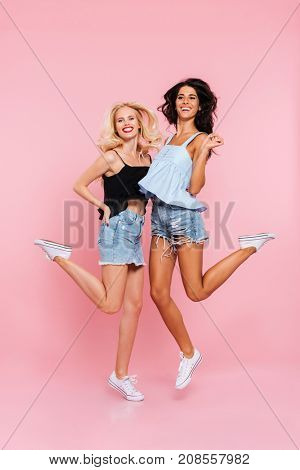 Full length image of two happy women in summer clothes rejoice and jumping while looking at the camera over pink background