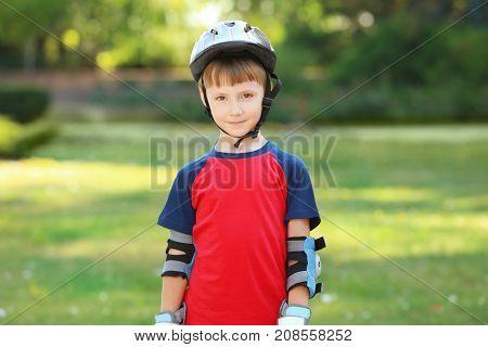 Cute boy rollerskating in park