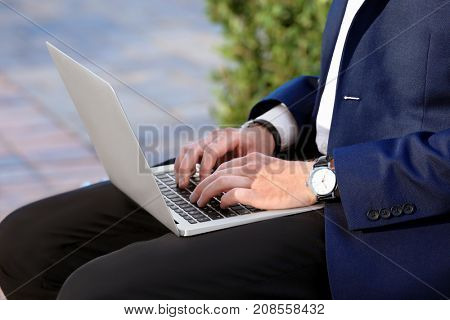 Stylish young man with laptop, outdoors