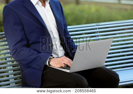 Stylish young man with laptop on bench, outdoors