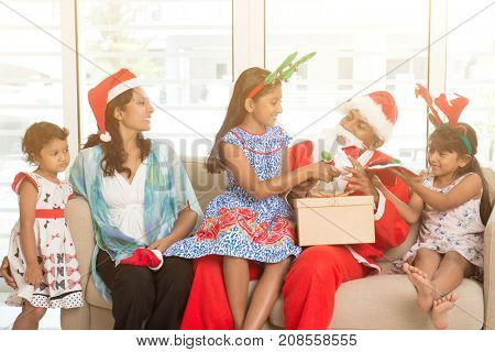 Happy Indian family celebrating Christmas day, with gift box and santa sitting on sofa or couch at home, Asian parents and children festival mood indoors.