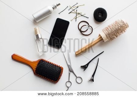 hair tools, beauty and hairdressing concept - smartphone, scissors, brushes and styling sprays with pins and ties on white background