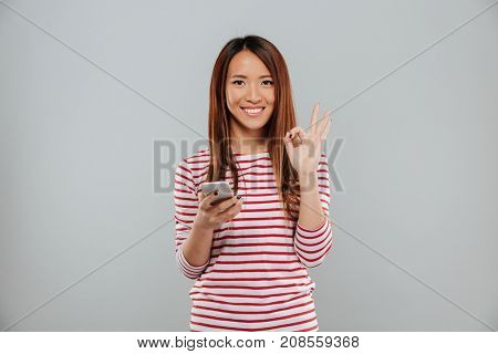 Picture of cheerful young asian woman chatting by phone standing isolated over grey wall. Looking camera showing okay gesture.