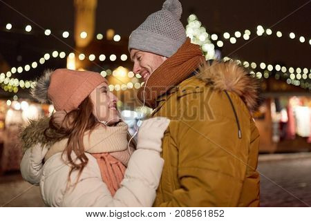 winter holidays and people concept - happy young couple with earphones dating at christmas square in evening