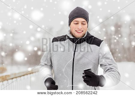 fitness, sport, people, technology and healthy lifestyle concept - happy young man in earphones with smartphone listening to music and running along winter road