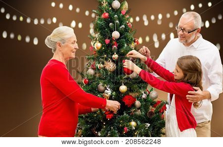 holidays, generation and people concept - happy family decorating christmas tree over lights background