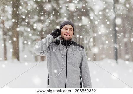 fitness, sport, people and healthy lifestyle concept - happy smiling young man with earphones listening to music in winter forest
