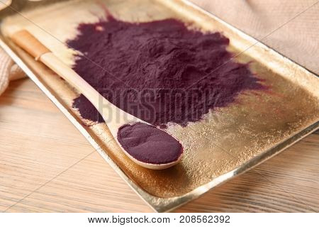 Metal tray with acai powder and spoon on wooden background